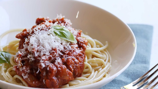 Deep red bolognase sauce over spaghetti with grated parmesan and fresh basil