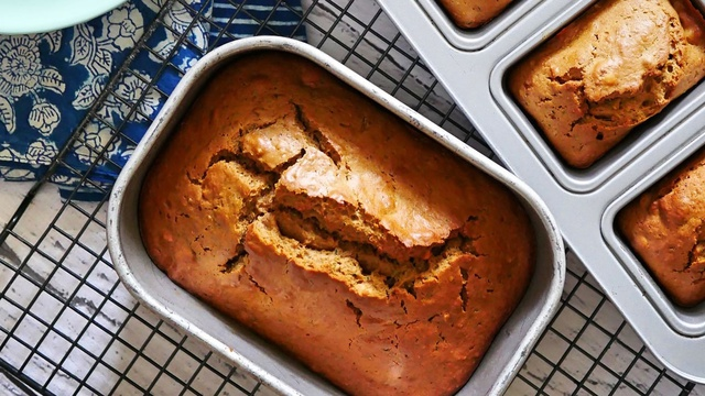 Large loaf tin with amber spiced zucchini bread beside individual loaves on a wire rack