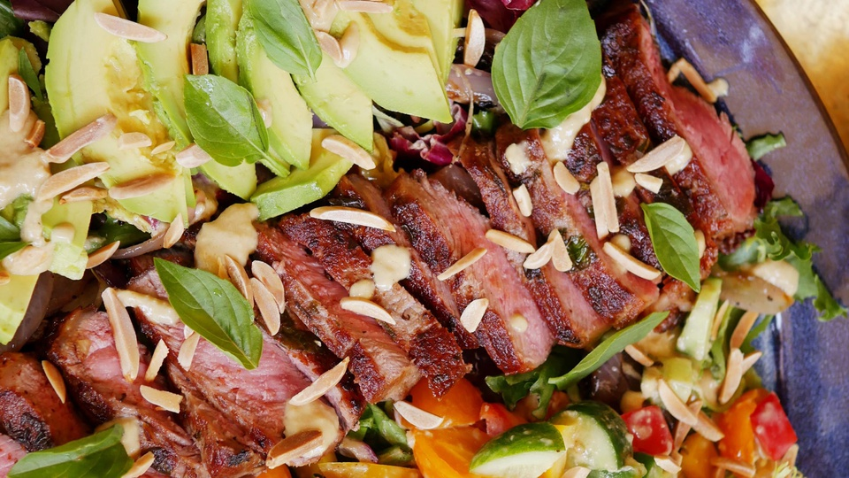 Medium-rare grilled steak on salad bed with avocado topped with slivered almonds