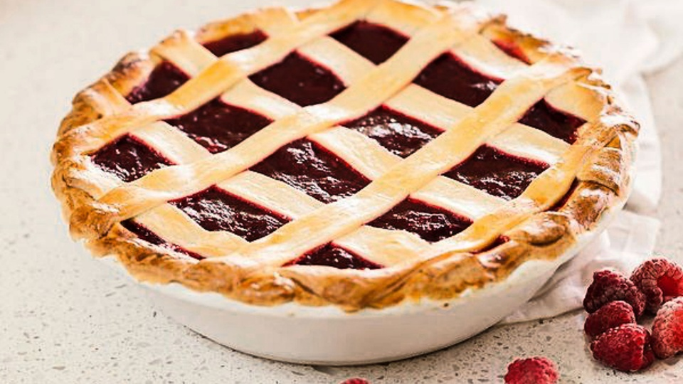 Classic latticed rhubarb strawberry pie with deep red filling and golden brown ruffled edges