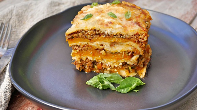 Cross section of orange brown and cream layers of lasagne stacked high garnished with fresh basil