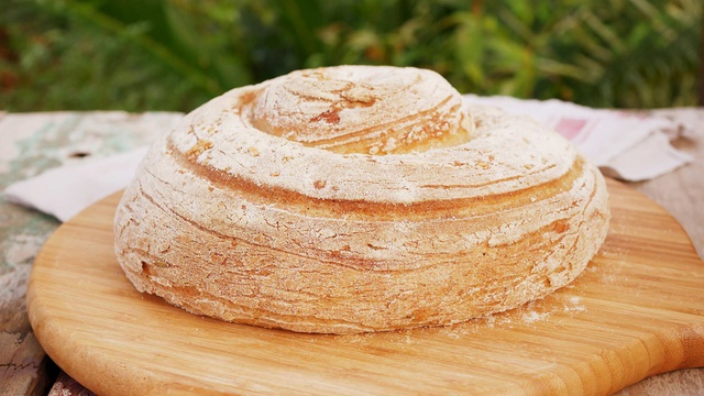 A wound floury loaf of rosemary and pink salt bread