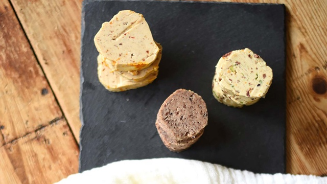 Three stacks of flavored butters served on slate tray