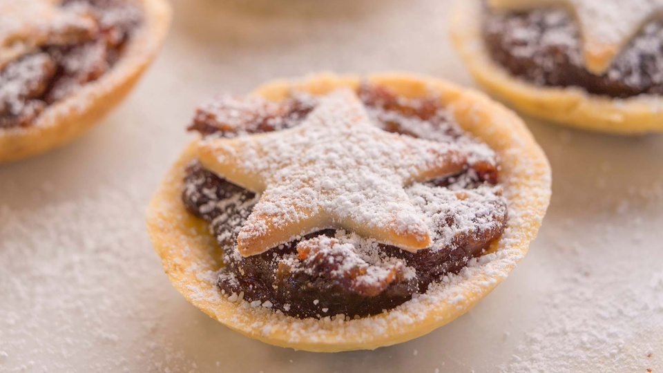 Mini mince pie topped with marzipan star and powdered sugar