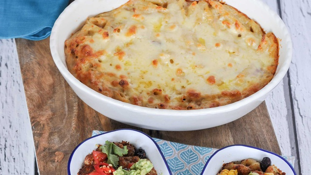 Oval baking dish holds golden brown creamy Greek pasta bake