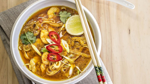 Bowl of mustard colored prawn and coconut laksa with noodles lime and fresh chilli