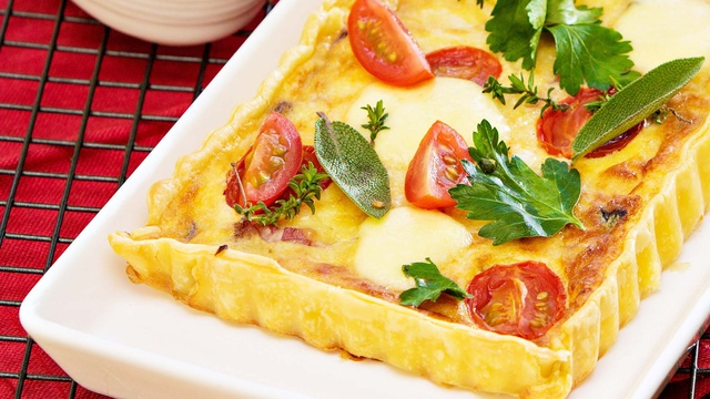 Shallow rectangular tart filled with speck cherry tomatoes and cheese