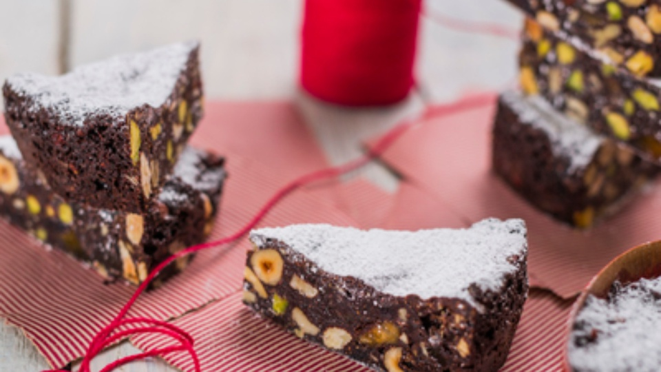 Thick segments of dense dark panforte filled with nuts and fruits topped with powdered sugar