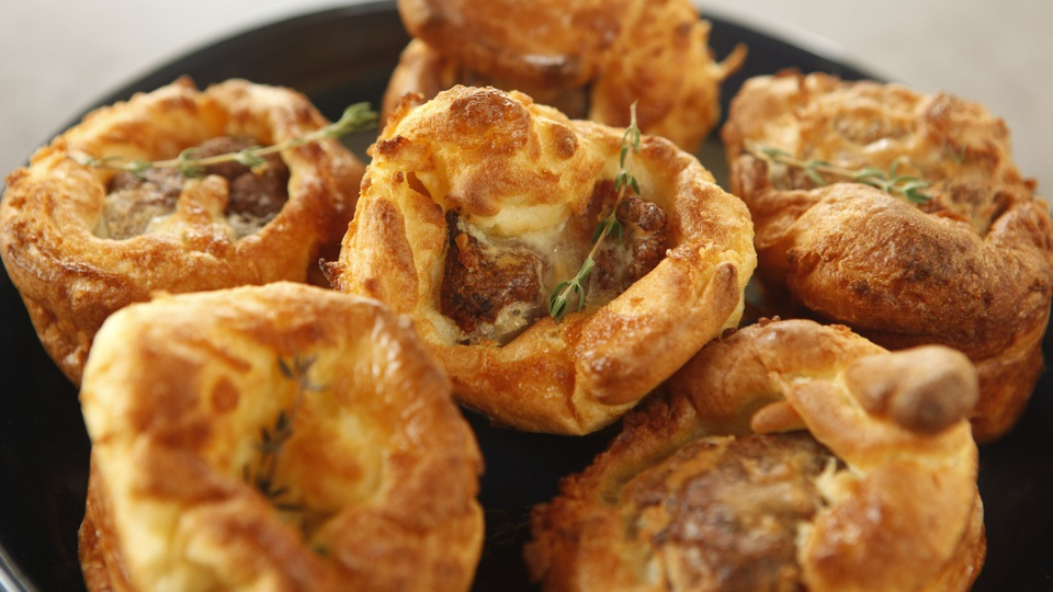Individual golden puffed pastries encase herbed chicken topped with thyme