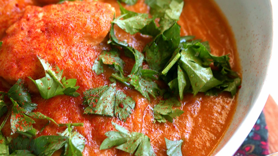 A large bowl of thick, burnt-orange colored sauce covers chicken thighs topped with plenty of parsley