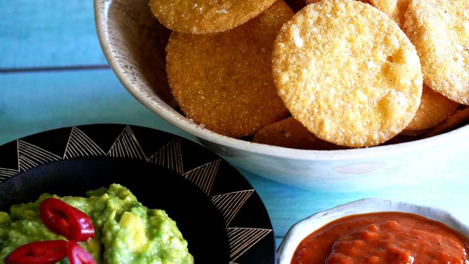 Circular corn chips fill a bowl with guacamole and salsa on the side