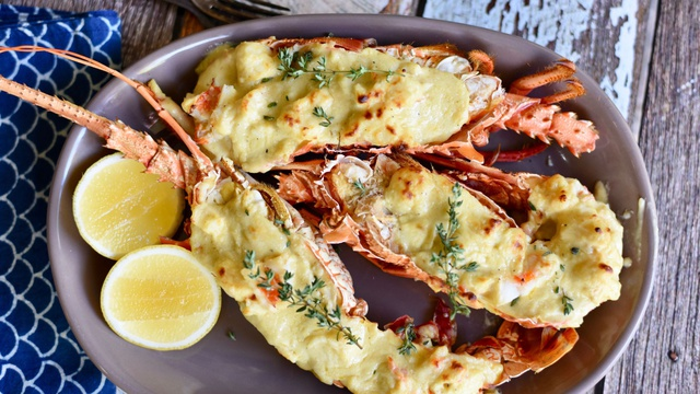 Pink lobster halves covered in melted cheese seasoned with sprigs of thyme and lime wedges