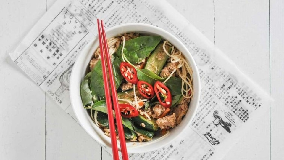 Crispy fried chicken sits in a bowl of egg noodles with zucchini Thai basil and slices of red chilli