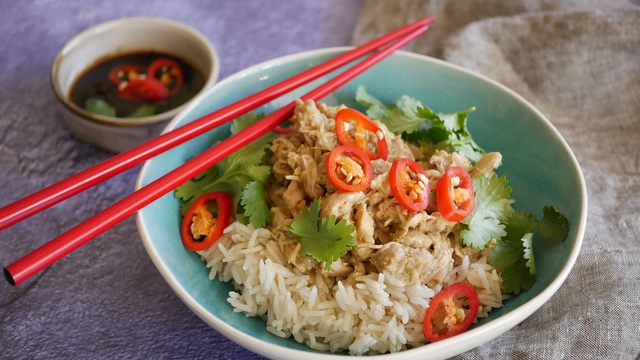 Bright slices of fresh chilli contrasts against shredded chicken and dirty rice beside dark soy dipping sauce