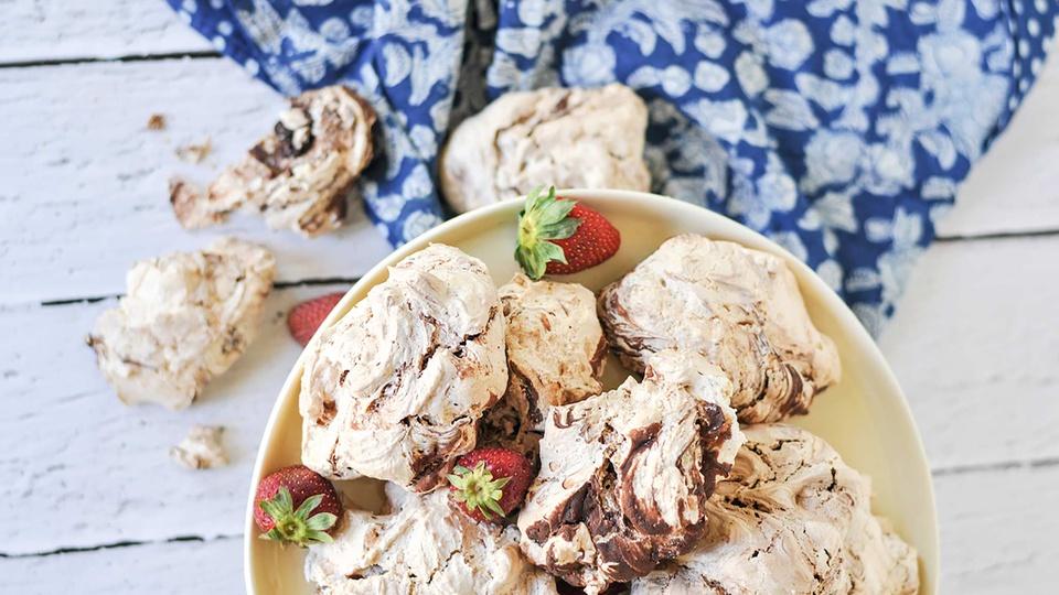 Cake stand of chocolate cinnamon swiss meringues with chocolate swirls and fresh strawberries