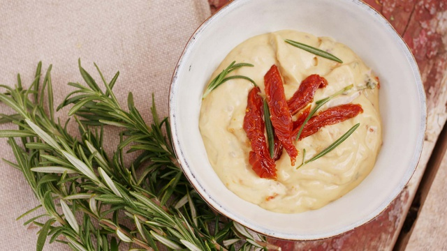 Bowl of thick mayo with fresh rosemary topped with slices of sundried tomatoes
