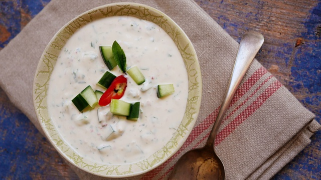 Serving bowl of minted white yogurt dip with cucumber chunks