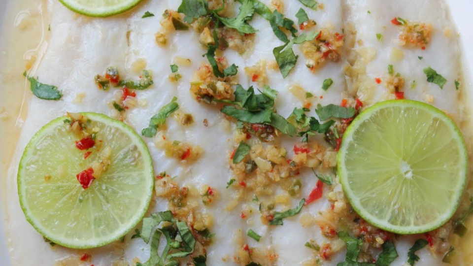 Close up of moist white fish with flecks of corriander, chilli and lime rounds
