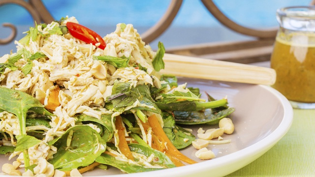 Large plate of shredded chicken carrot and spinach salad with Vietnamese dressing and peanuts