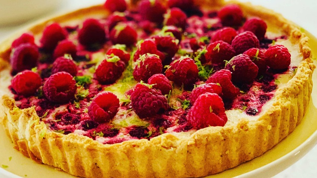 Shortcrust pastry flan of lime and raspberry filling with fresh raspberries and lime zest