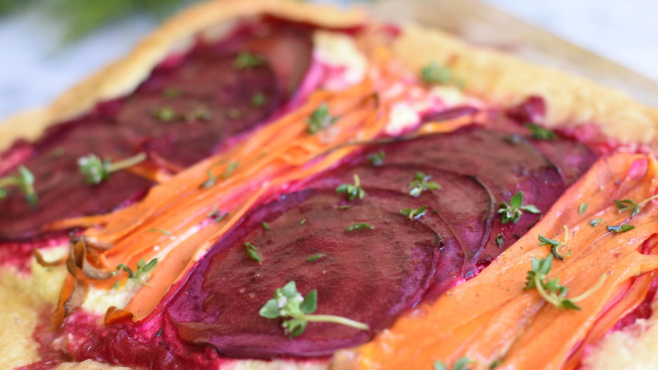 Vibrant magenta rounds of beetroot beside bright orange carrots nestled in ricotta surrounded by pastry