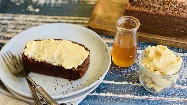 Thick slice of nutty brown date and honey loaf served with honey and whipped butter