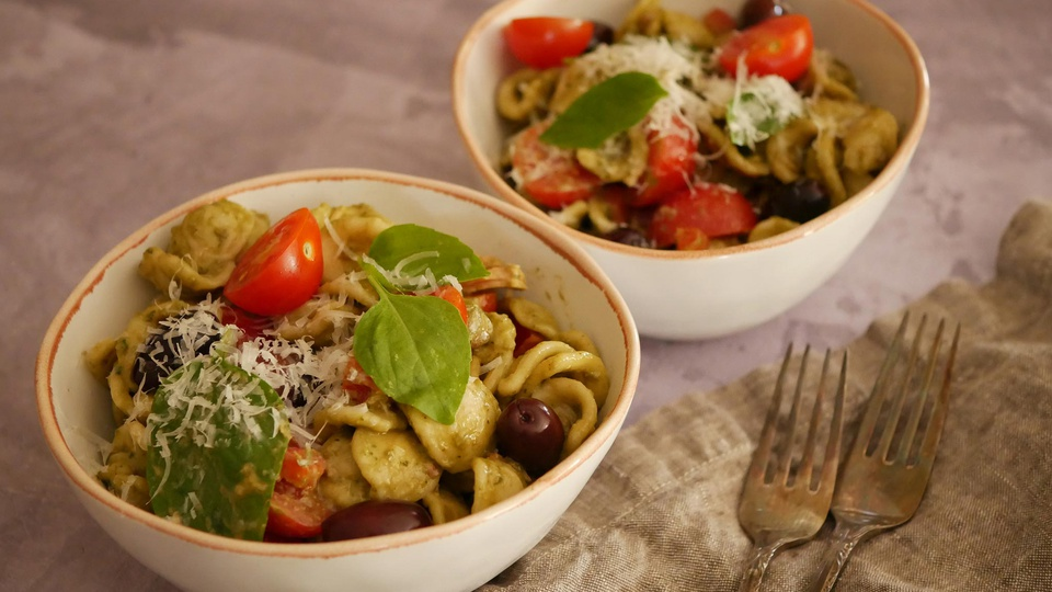 Bowls of dressed pasta salad with tomatoes olives fresh basil and parmesan