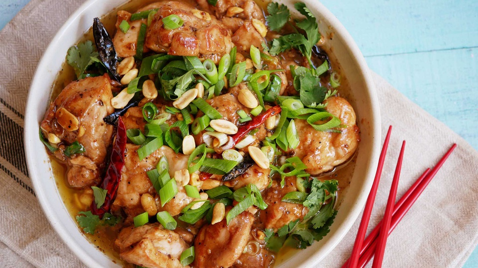 Sticky orange chicken in kung pao glaze fills a family style bowl sprinkled with scallions and peanuts