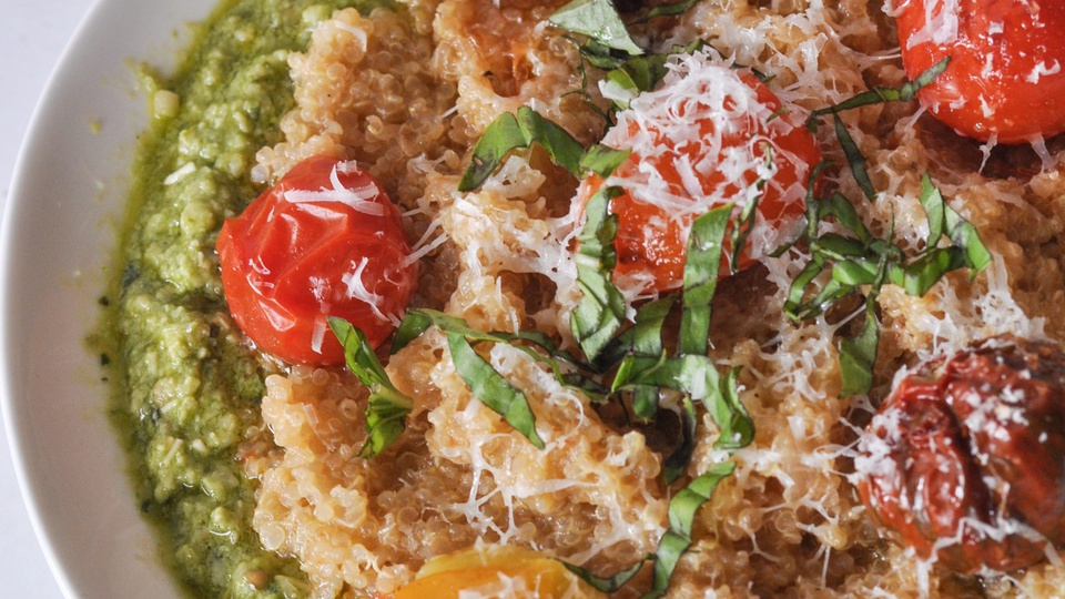 Two-toned pesto and tomato quinoa is covered in cherry tomatoes and grated parmesan