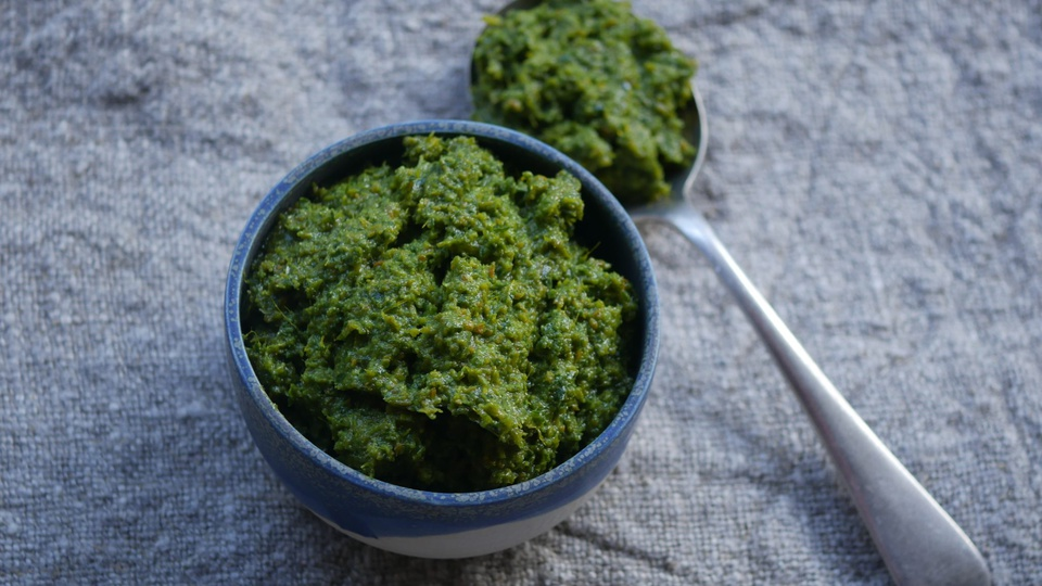Forest green thai curry paste served in a small clay ramekin