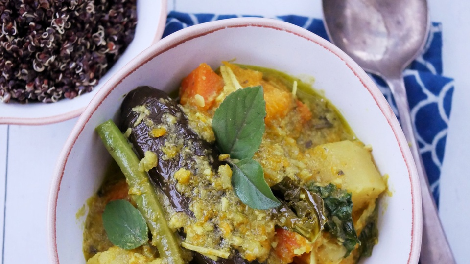 Green Thai curry with carrots potatoes and eggplant served in a bowl with black quinoa