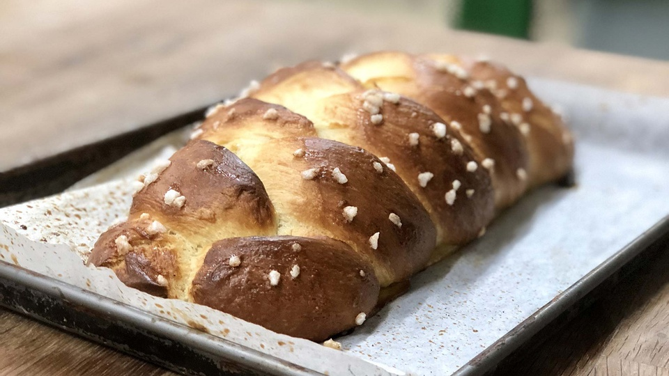 A plait of golden brown brioche with sugar crystals on top fresh on a baking tray