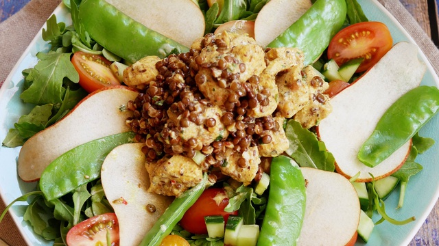 Curried chicken sits in the centre of an ornate plating of pear slices rocket cherry tomatoes and lentils