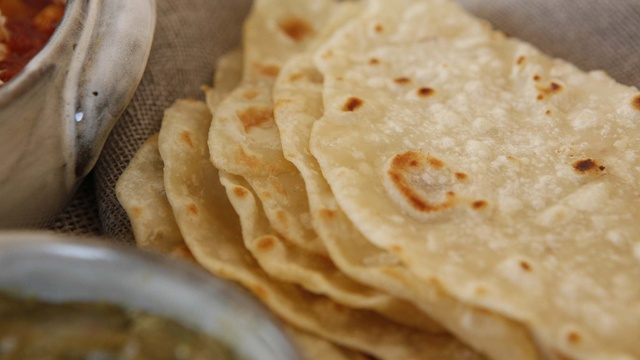 Layers of white flour and duck fat tortillas have circles of toasted brown and black