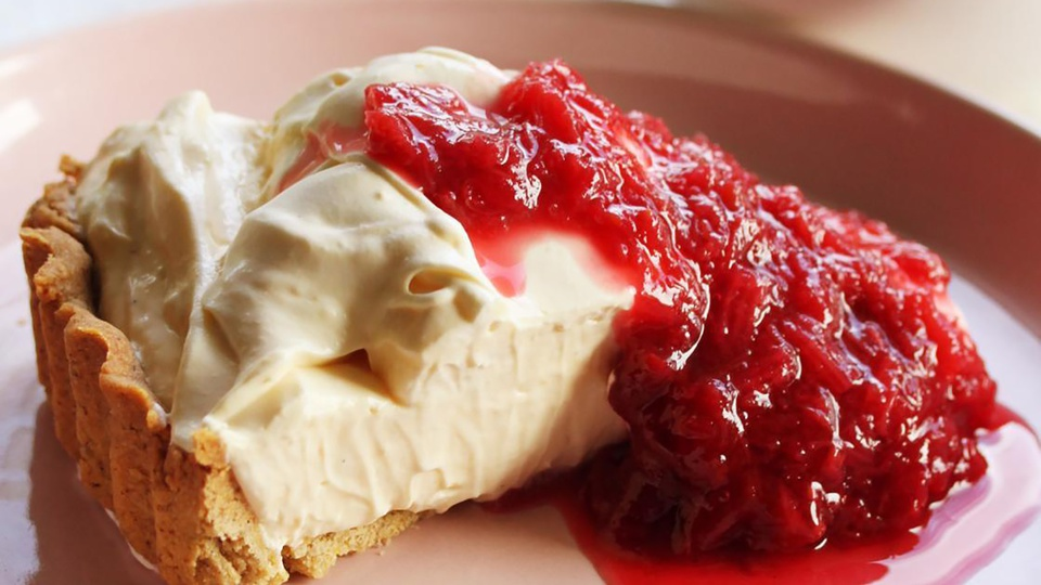 Lemon tart overflows with creamy filling and rhubarb raspberry compote