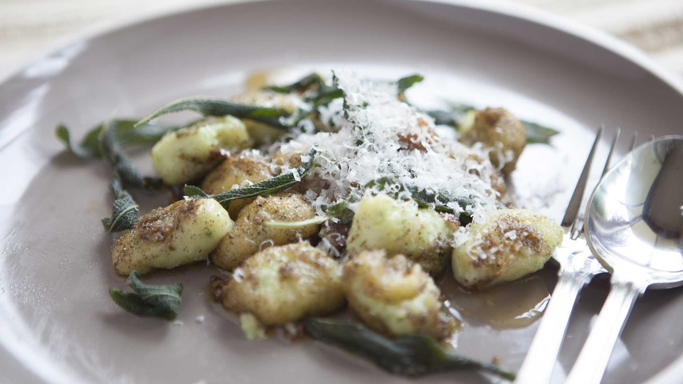 Yellow gnocci in a deep brown butter sauce with sage leaves and grated parmesan