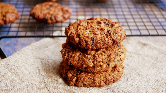 Stack of three brown chewy oatmeal cookies with currants