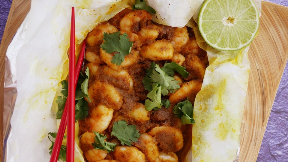 Parcel filled with grilled prawns in a red speckled sauce garnished with a lime and coriander