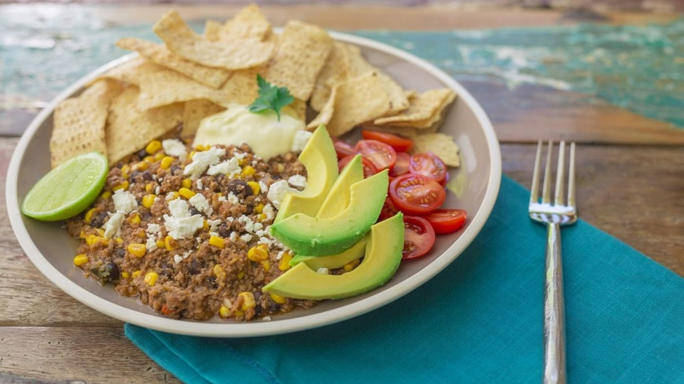 Deep browned beef black beans and corn with nachos avocado tomatoes and a dollop of sour cream
