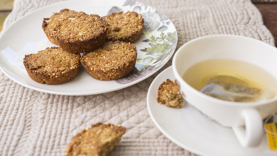 Plate of browned thick coins of granuesli breakfast bars served with lemon tea