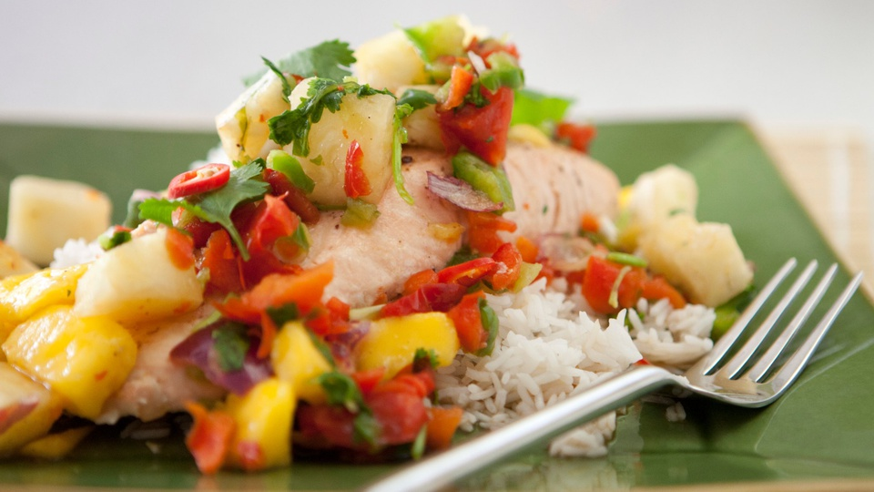 Green red and yellow mango salsa tops pink steamed salmon on fluffy white rice