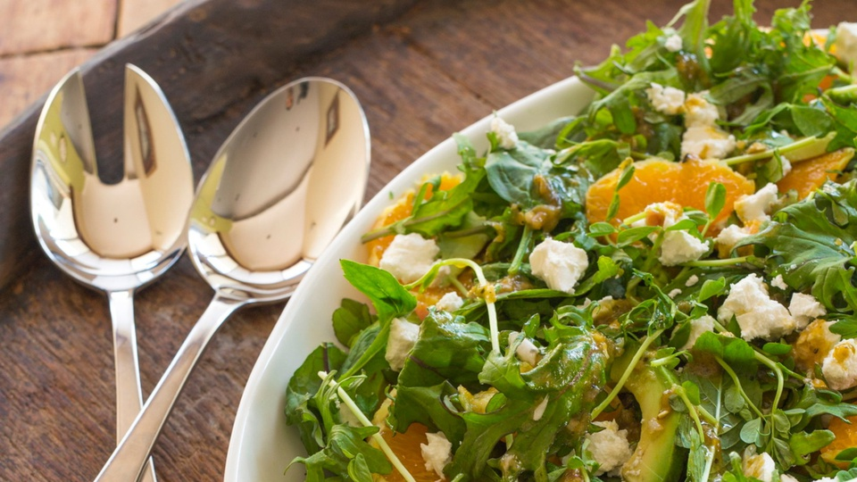 Serving plate of leafy green salad with clumps of feta and mandarin with avocado and microgreens