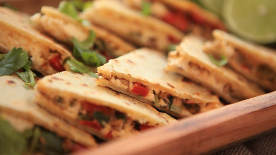 Stacks of toasted quesadillas filled with cheese, peppers and sprinkled with parsley