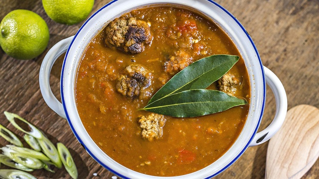 Family style pot of chilli con carne with browned meatballs and bay leaves