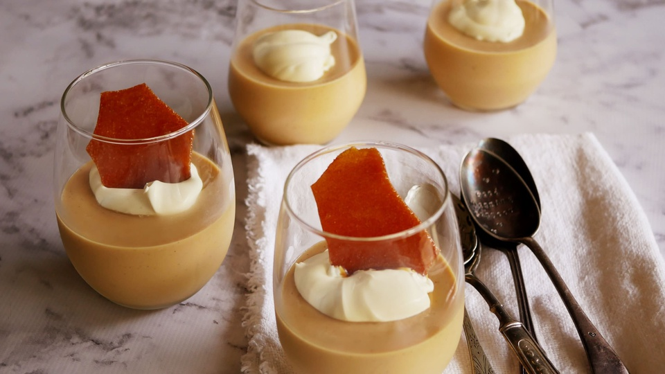 Glasses of creamy chilled caramel served with cream and caramel brittle