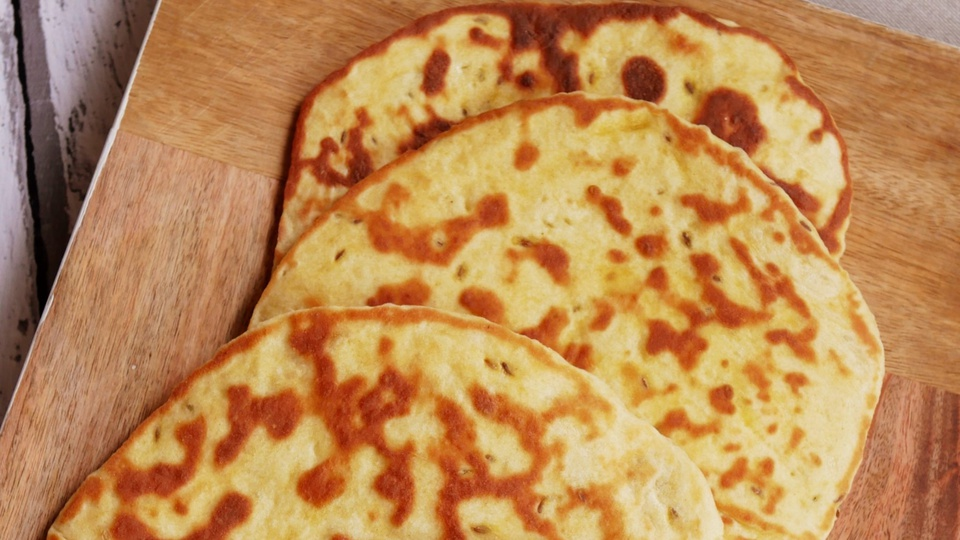 Yellow rounds of cumin flatbreads with patterned browning