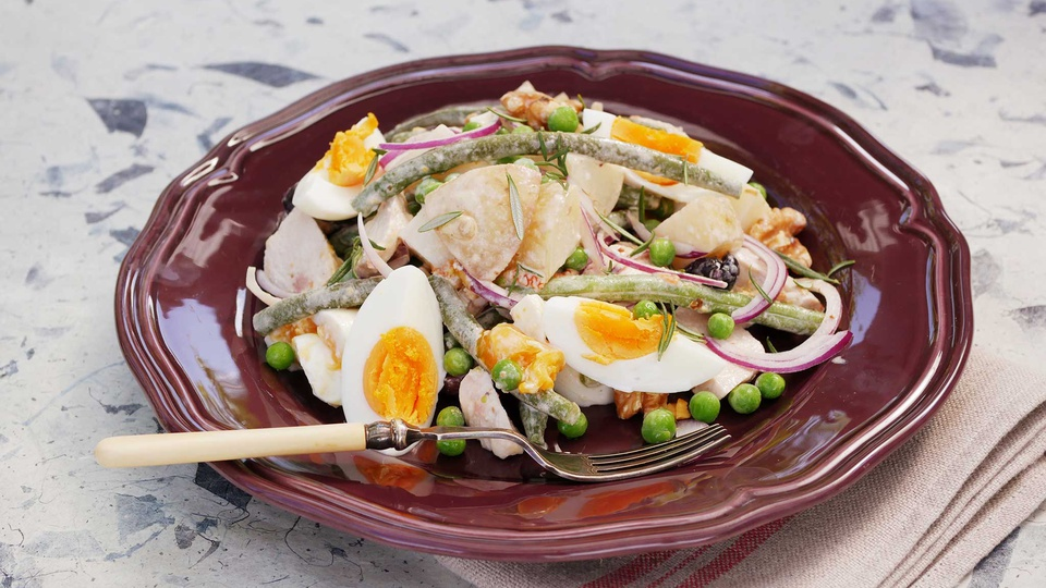 Chicken and potato salad with green beans golden boiled eggs and slices of red onion