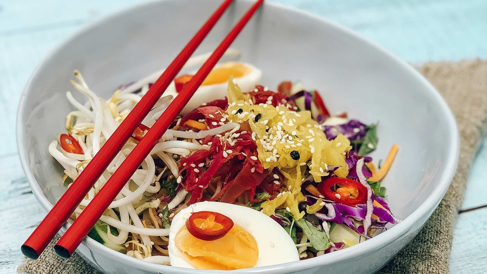 Red chilli, purple cabbage, orange egg yolks, brown noodles and white bean sprouts are mixed in a white bowl