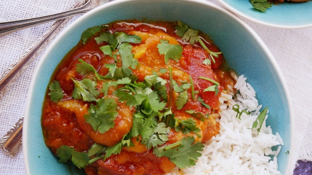 Vibrant apricot curry covers moist chicken served in a bowl of fluffy rice