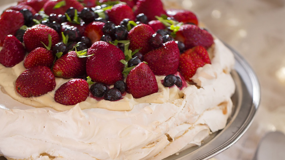 Strawberries blueberries and mint top a crunchy fluffy Christmas pavlova